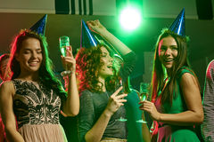 Smiling friends with glasses of champagne in club Stock Images