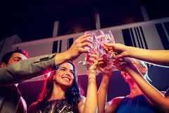 Smiling friends with glasses of champagne in club Stock Image