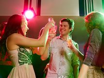 Smiling friends with glasses of champagne in club Stock Photos