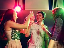 Smiling friends with glasses of champagne in club Stock Photography