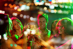 Smiling friends with glasses of champagne in club. Party, holidays, celebration, nightlife and people concept - smiling friends clinking glasses of champagne in Stock Images