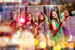 Smiling friends with glasses of champagne in club Royalty Free Stock Images
