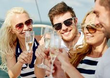 Smiling friends with glasses of champagne on yacht Stock Images