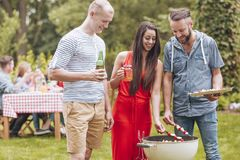 Smiling friends grilling shashliks and drinking beer during garden party. Photo concept royalty free stock image