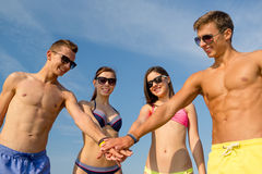 Smiling friends with hand on top outdoors. Friendship, sea, holidays, gesture and people concept - group of smiling friends wearing swimwear and sunglasses royalty free stock images