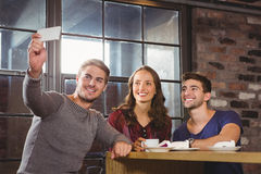 Smiling friends having coffee and taking selfies Royalty Free Stock Images