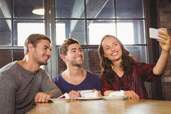 Smiling friends having coffee and taking selfies Stock Photos