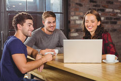 Smiling friends having coffee together and looking at laptop Royalty Free Stock Photo