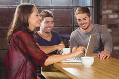 Smiling friends having coffee together and looking at laptop. At coffee shop Stock Images