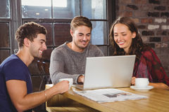 Smiling friends having coffee together and looking at laptop. At coffee shop Stock Photos