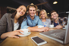 Smiling friends having coffee together Royalty Free Stock Photos