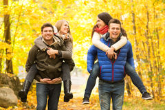 Smiling friends having fun in autumn park Stock Images