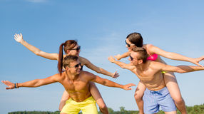 Smiling friends having fun on summer beach. Friendship, sea, summer vacation, holidays and people concept - group of smiling friends wearing swimwear and royalty free stock photo