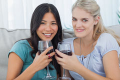 Smiling friends having red wine together looking at camera Stock Photos