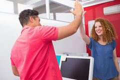 Smiling friends high fiving together Stock Photos