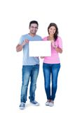 Smiling friends holding blank sign together Stock Photos