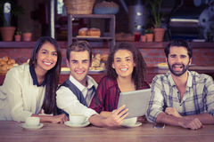 Smiling friends holding a digital tablet Stock Photo