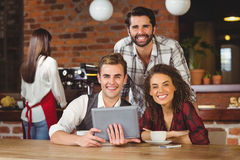 Smiling friends holding a digital tablet Royalty Free Stock Photos