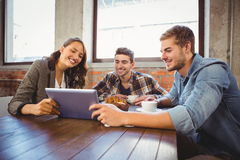 Smiling friends holding tablet and looking at it Royalty Free Stock Image