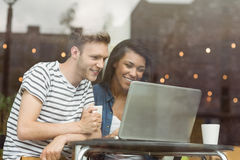 Smiling friends with a hot drink using laptop Stock Photos