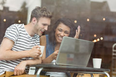 Smiling friends with a hot drink using laptop Royalty Free Stock Images