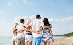 Smiling friends hugging and walking on beach Stock Photos