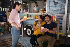 Friends interacting with each other in food truck van. Smiling friends interacting with each other in food truck van royalty free stock photo