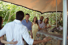 Smiling friends interacting while having a champagne at counter. In restaurant Royalty Free Stock Photography