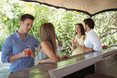 Smiling friends interacting while having a cocktail at counter Royalty Free Stock Image