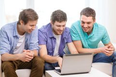 Smiling friends with laptop computer at home. Friendship, technology and home concept - smiling male friends with laptop computer at home royalty free stock photos