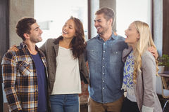 Smiling friends laughing and putting arms around each other Stock Photos