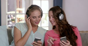Smiling friends listening music with headphones stock video footage
