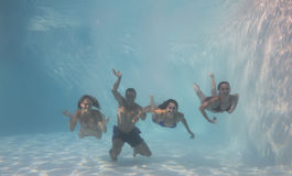 Smiling friends looking at camera underwater in swimming pool Stock Photos