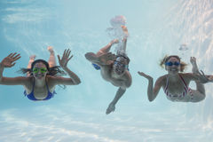 Smiling friends looking at camera underwater in swimming pool Royalty Free Stock Photos