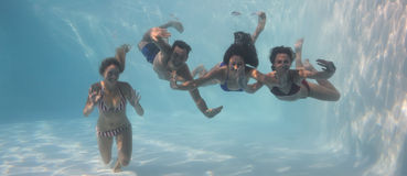 Smiling friends looking at camera underwater in swimming pool Stock Image