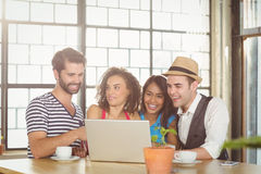Smiling friends looking at laptop and having coffee Royalty Free Stock Image