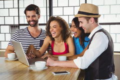 Smiling friends looking at laptop and having coffee Stock Photography