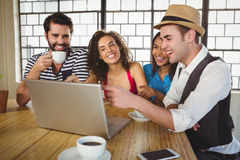Smiling friends looking at laptop and having coffee Royalty Free Stock Photo