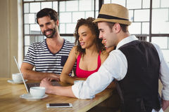 Smiling friends looking at laptop and having coffee Stock Photo