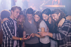 Smiling friends looking at smart phone in nightclub. Smiling friends looking at smart phone while standing in nightclub Stock Images
