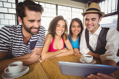 Smiling friends looking at tablet computer Stock Image