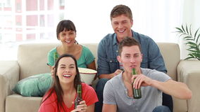 Smiling friends looking at the television while laughing Stock Image