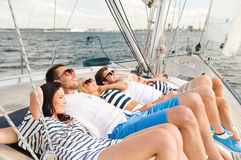 Smiling friends lying on yacht deck Royalty Free Stock Image
