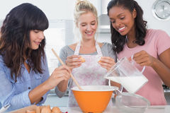 Smiling friends making pastry together Royalty Free Stock Image