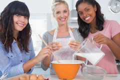 Smiling friends making pastry together looking at camera Stock Images