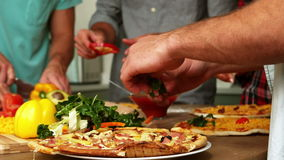 Smiling friends making pizza together stock video footage