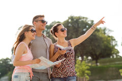 Smiling friends with map and city guide outdoors Stock Photography