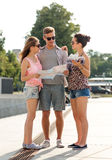 Smiling friends with map and city guide outdoors Stock Photos