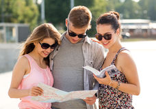 Smiling friends with map and city guide outdoors Royalty Free Stock Image