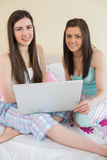 Smiling friends in pajamas talking on bed using a laptop looking Royalty Free Stock Photo